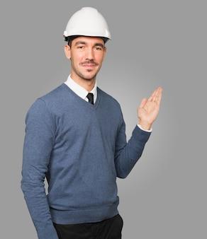 Młody architekt gestem powitania ręką