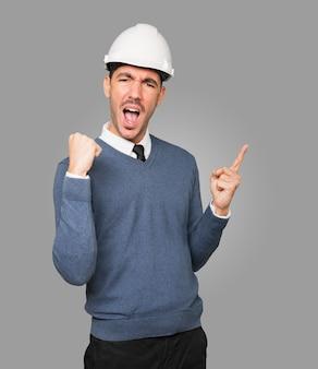 Młody architekt gestem świętowania i wskazując palcem