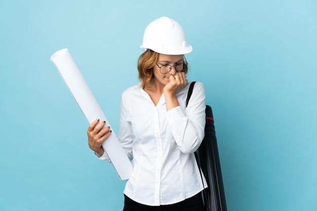 Młody architekt gruzińska kobieta w kasku i trzymając plany na białym tle ma wątpliwości
