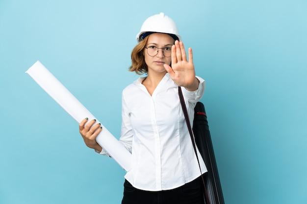 Młody architekt gruziński kobieta z hełmem i gospodarstwa plany na białym tle