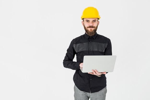Młody architekt jest ubranym żółtego hardhat mienia przenośnego laptop