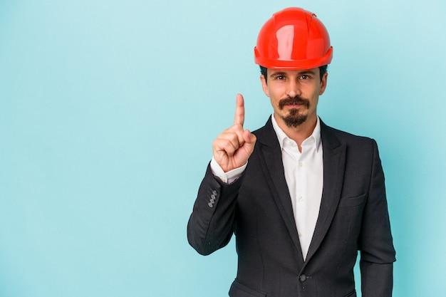 Młody architekt kaukaski mężczyzna na białym tle na niebieskim tle pokazując numer jeden palcem.