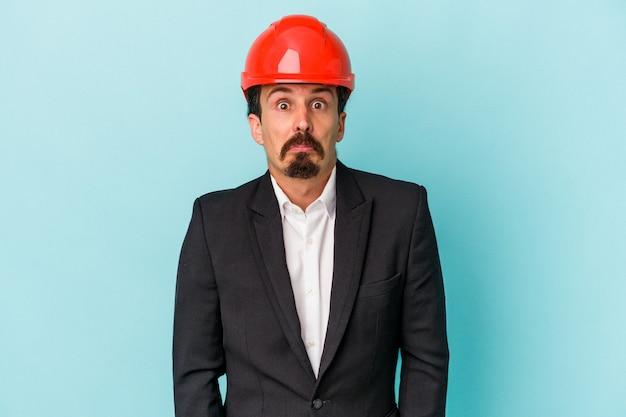 Młody architekt kaukaski mężczyzna na białym tle na niebieskim tle wzrusza ramionami i otwiera oczy zdezorientowany.