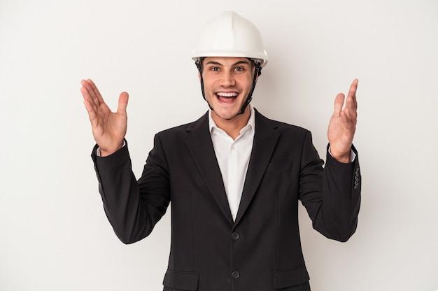 Młody architekt kaukaski mężczyzna na białym tle odbiera miłą niespodziankę, podekscytowany i podnosząc ręce.