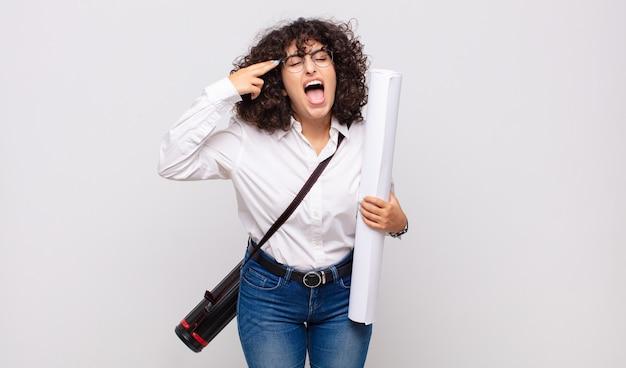 Młody architekt kobieta szuka nieszczęśliwego i zestresowanego, samobójczy gest czyniąc znak pistoletu ręką, wskazując na głowę