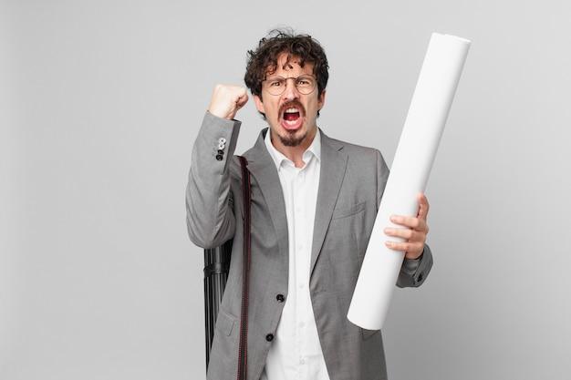 Młody architekt krzyczy agresywnie z gniewnym wyrazem twarzy