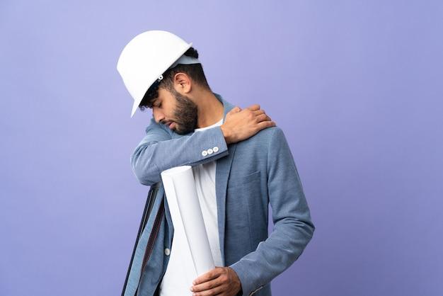 Młody architekt marokański mężczyzna z hełmem i trzymający plany na białym tle, cierpiący na ból w ramieniu za wysiłek