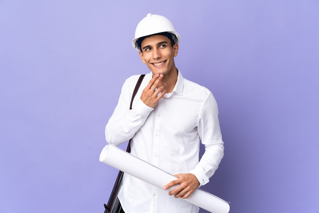 Młody architekt mężczyzna na białym tle na tle patrząc uśmiechnięty