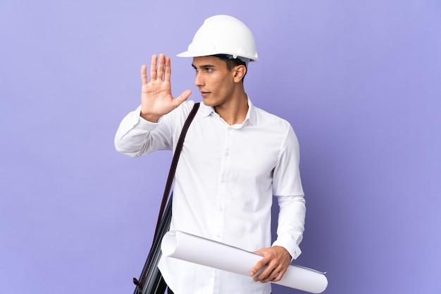 Młody architekt mężczyzna na białym tle na tle robi gest stop i rozczarowany