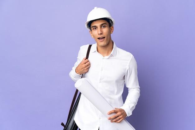 Młody architekt mężczyzna na białym tle z zaskoczeniem wyraz twarzy