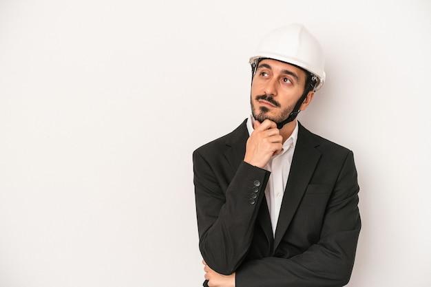 Młody architekt mężczyzna ubrany w kask budowlany na białym tle patrząc w bok z wyrazem wątpliwości i sceptyczny.