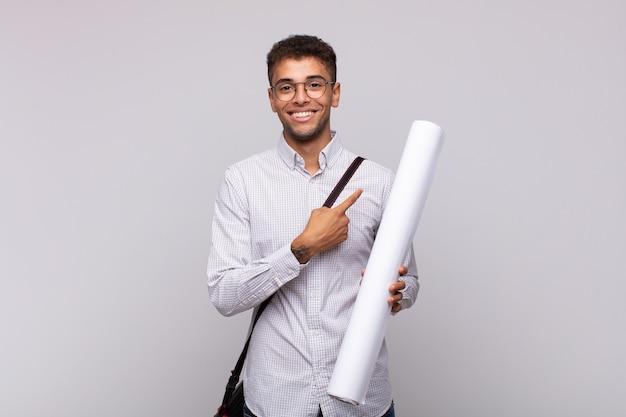 Młody architekt mężczyzna uśmiecha się radośnie, czuje się szczęśliwy i wskazuje na bok i do góry