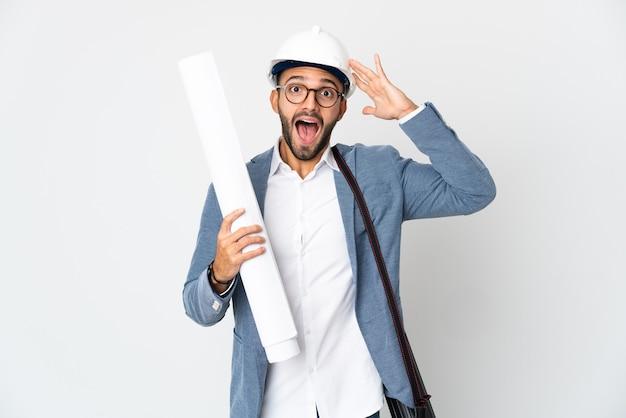 Młody architekt mężczyzna z hełmem i trzymając plany na białym tle