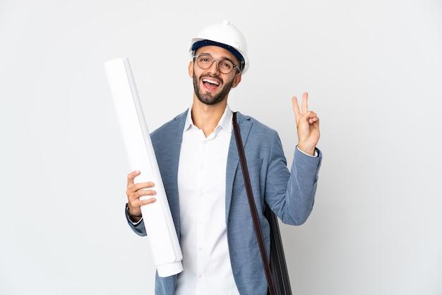 Młody architekt mężczyzna z hełmem i trzymający plany na białym tle uśmiechający się i pokazujący znak zwycięstwa