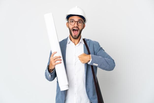 Młody architekt mężczyzna z hełmem i trzymający plany na białym tle z niespodzianką wyrazem twarzy