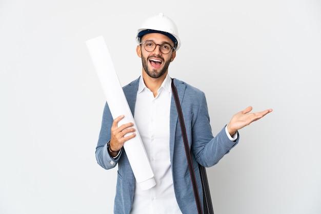 Młody architekt mężczyzna z hełmem i trzymający plany na białym tle z zszokowanym wyrazem twarzy