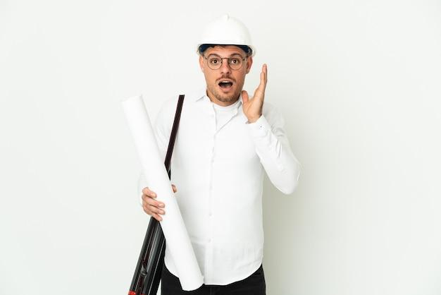 Młody architekt mężczyzna z hełmem i trzymający plany na białym tle
