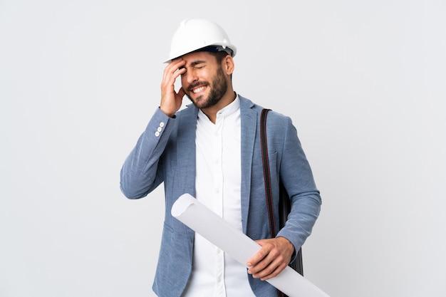 Młody architekt mężczyzna z kaskiem i trzymając plany na białym, śmiejąc się
