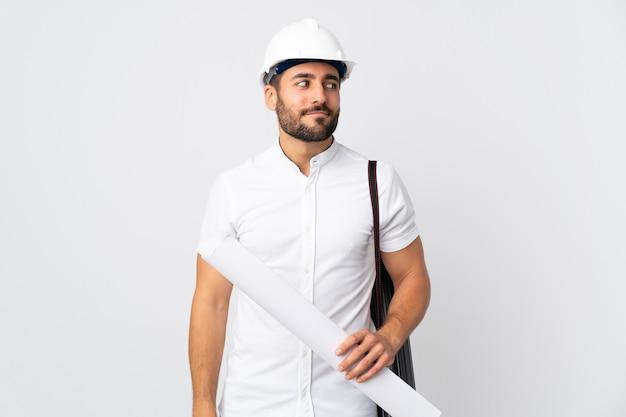 Młody architekt mężczyzna z kaskiem i trzymając plany na białym tle, mając wątpliwości, patrząc z boku