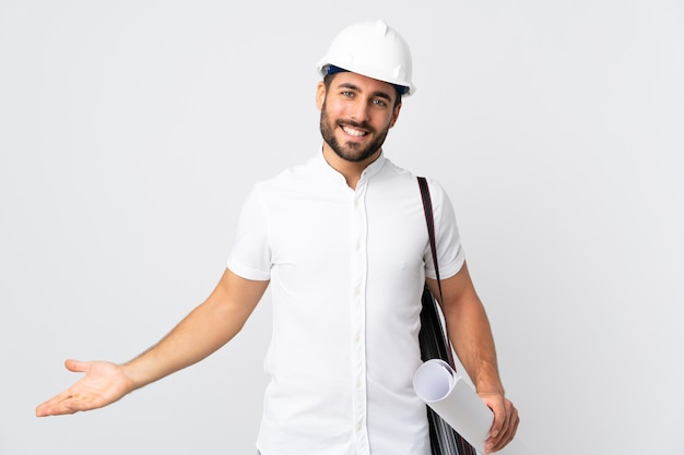 Młody architekt mężczyzna z kaskiem i trzymając plany na białym tle, mając wątpliwości