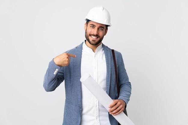 Młody architekt mężczyzna z kaskiem i trzymając plany na białym tle na białej ścianie dumny i zadowolony z siebie