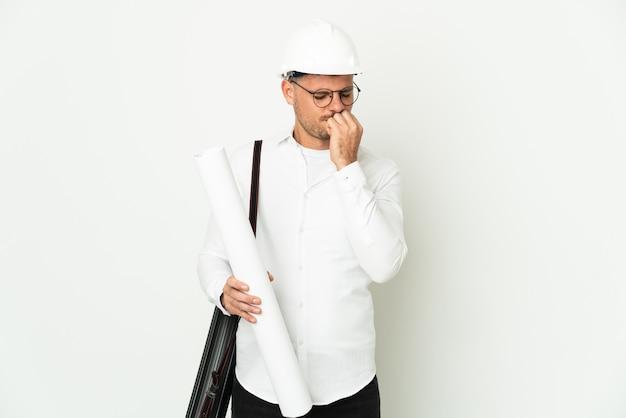 Młody architekt mężczyzna z kaskiem i trzymając plany na białym tle na białym tle, mając wątpliwości