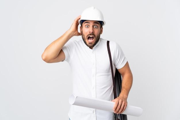 Młody architekt mężczyzna z kaskiem i trzymając plany na białym tle na białym tle robi nerwowy gest