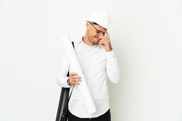 Młody architekt mężczyzna z kaskiem i trzymając plany na białym tle na białym tle, śmiejąc się