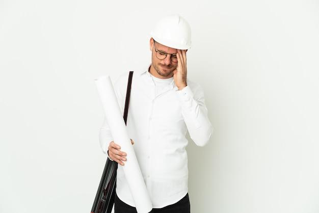 Młody architekt mężczyzna z kaskiem i trzymając plany na białym tle na białym tle z wypowiedzi zmęczony i chory