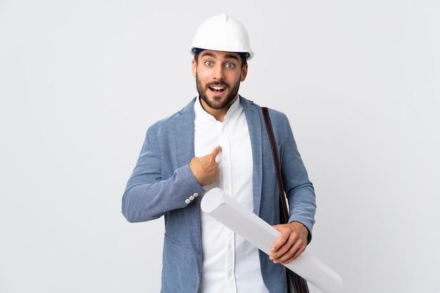 Młody architekt mężczyzna z kaskiem i trzymając plany na białym tle na białym tle z zaskoczeniem wyraz twarzy