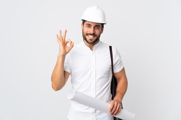Młody architekt mężczyzna z kaskiem i trzymając plany na białym tle pokazano znak ok palcami