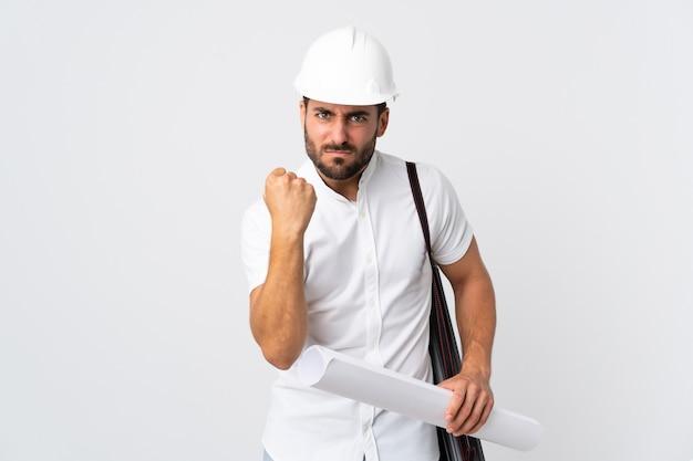 Młody architekt mężczyzna z kaskiem i trzymając plany na białym tle z nieszczęśliwym wyrazem