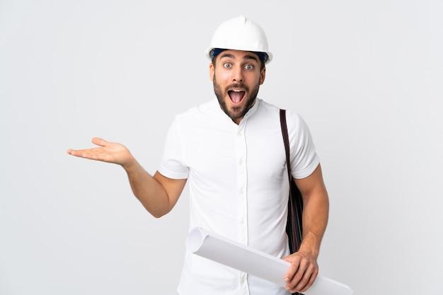 Młody architekt mężczyzna z kaskiem i trzymając plany na białym tle z zszokowany wyraz twarzy