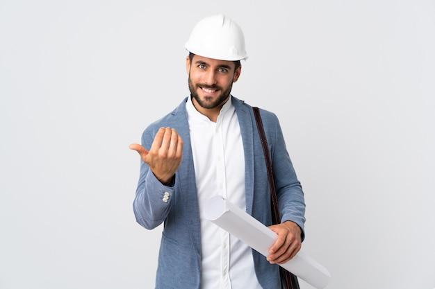 Młody architekt mężczyzna z kaskiem i trzymając plany na białym, zapraszając do przyjścia z ręką. cieszę się, że przyszedłeś