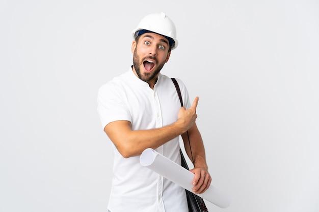 Młody architekt mężczyzna z kaskiem i trzymając plany na białym zaskoczony i wskazując stronę