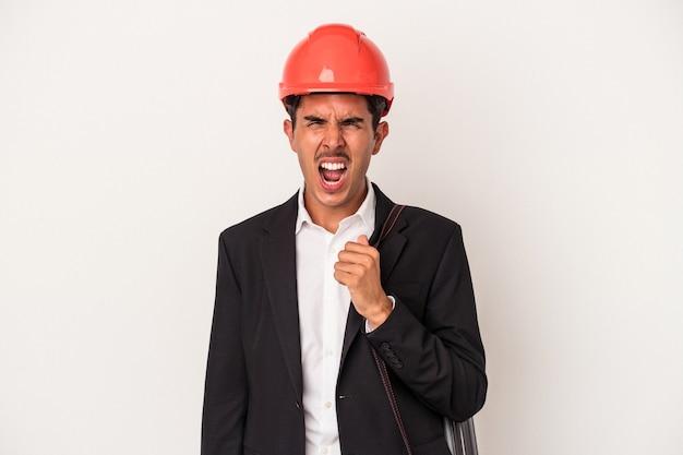 Młody architekt mieszany człowiek rasy na białym tle krzyczy bardzo zły i agresywny.