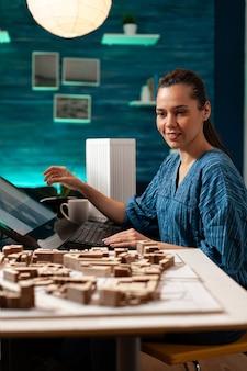 Młody architekt pracujący nad budową miniaturowej makiety
