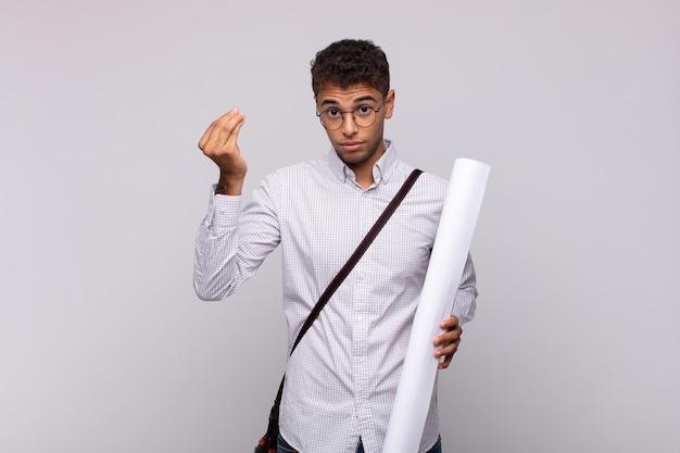Młody architekt robi gest kaprysu lub pieniędzy, mówi, że masz spłacić swoje długi!