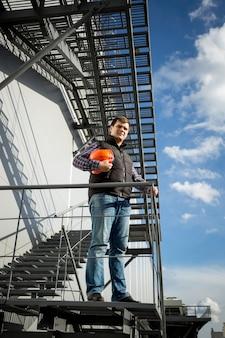 Młody architekt stojący na metalowych schodach z boku fabryki