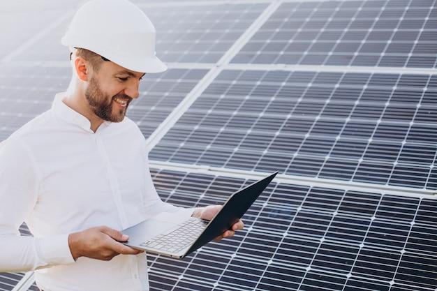 Młody architekt stojący przy panelach słonecznych wykonujący diagnostykę na komputerze