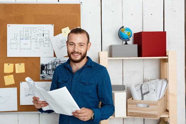 Młody architekt sukcesu, uśmiechnięty, trzymając rysunki, stojąc w ścianie biura