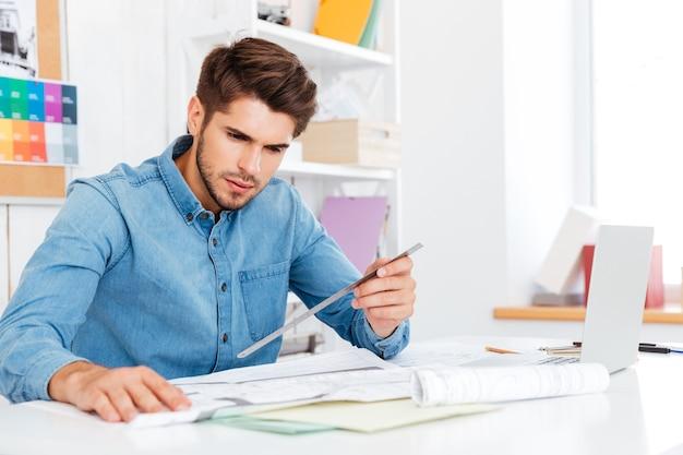 Młody architekt trzymający linijkę nad diagramem na biurku