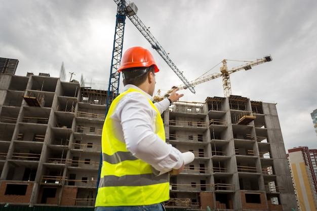 Młody architekt trzymający plany i wskazujący na budynek w budowie