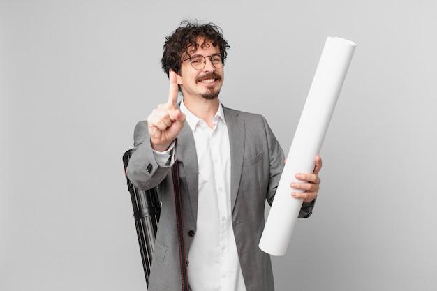 Młody architekt uśmiechający się dumnie i pewnie robiący numer jeden