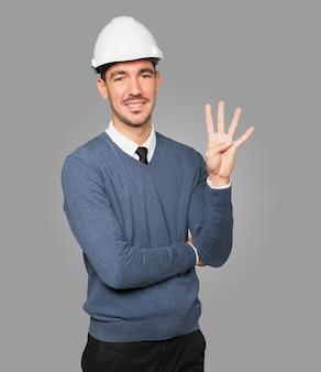 Młody architekt wykonujący gest numer cztery