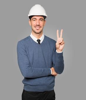 Młody architekt wykonujący gest numer dwa