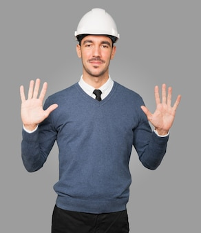 Młody architekt wykonujący gest numer dziesięć