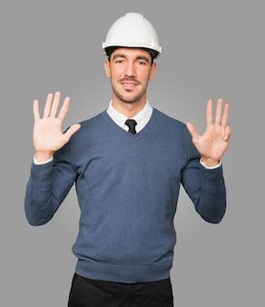 Młody architekt wykonujący gest numer dziewięć