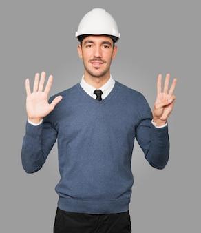Młody architekt wykonujący gest numer osiem