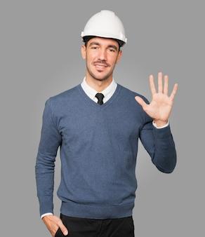 Młody architekt wykonujący gest numer pięć